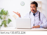 Young doctor listening to patient during telemedicine session. Стоковое фото, фотограф Elnur / Фотобанк Лори