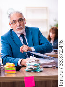Купить «Two employees and excessive work in the office», фото № 33872416, снято 15 октября 2019 г. (c) Elnur / Фотобанк Лори