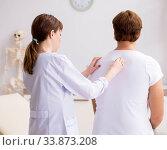 Купить «Male patient visiting young female doctor chiropractor», фото № 33873208, снято 29 августа 2018 г. (c) Elnur / Фотобанк Лори