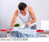 Купить «Young man freelancer ironing in the bedroom», фото № 33873804, снято 27 июня 2018 г. (c) Elnur / Фотобанк Лори