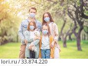 Adorable family in blooming cherry garden in masks. Стоковое фото, фотограф Дмитрий Травников / Фотобанк Лори