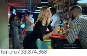 Купить «Cheerful young man flirting with women bar counter and drinking cocktails at nightclub», видеоролик № 33874368, снято 2 июля 2020 г. (c) Яков Филимонов / Фотобанк Лори