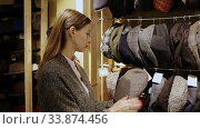 Купить «Young focused woman shopping hats in modern store», видеоролик № 33874456, снято 27 июня 2020 г. (c) Яков Филимонов / Фотобанк Лори