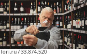 Portrait of senior man professional sommelier tasting red wines in wine store. Стоковое видео, видеограф Яков Филимонов / Фотобанк Лори