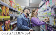 Купить «Portrait of young loving couple walking among shelves with groceries in supermarket», видеоролик № 33874584, снято 7 июля 2020 г. (c) Яков Филимонов / Фотобанк Лори