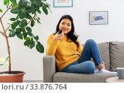Купить «asian woman with tv remote sitting on sofa at home», фото № 33876764, снято 14 марта 2020 г. (c) Syda Productions / Фотобанк Лори