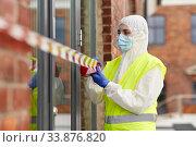 Купить «healthcare worker sealing door with caution tape», фото № 33876820, снято 24 апреля 2020 г. (c) Syda Productions / Фотобанк Лори