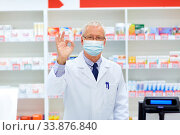 senior apothecary in mask at pharmacy showing ok. Стоковое фото, фотограф Syda Productions / Фотобанк Лори