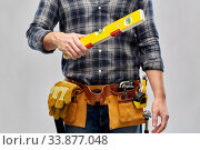 Купить «male builder with level and working tools on belt», фото № 33877048, снято 21 ноября 2019 г. (c) Syda Productions / Фотобанк Лори