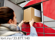 woman putting box to automated parcel machine. Стоковое фото, фотограф Syda Productions / Фотобанк Лори