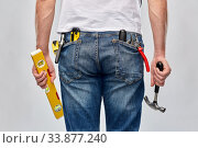 Купить «man with level and working tools in pockets», фото № 33877240, снято 21 ноября 2019 г. (c) Syda Productions / Фотобанк Лори