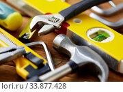 Купить «different work tools on wooden boards background», фото № 33877428, снято 26 ноября 2019 г. (c) Syda Productions / Фотобанк Лори