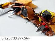 Купить «different work tools in belt on white background», фото № 33877564, снято 26 ноября 2019 г. (c) Syda Productions / Фотобанк Лори