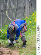 Электрик надевает на сапоги монтерские когти, чтобы с их помощью подняться на деревянный столб. Редакционное фото, фотограф Мария / Фотобанк Лори