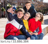 Four young happy teenagers taking self picture using mobile phone outdoors. Стоковое фото, фотограф Яков Филимонов / Фотобанк Лори