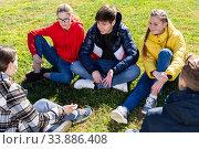 Купить «Cheerful teens sitting on green lawn and talking», фото № 33886408, снято 4 июня 2020 г. (c) Яков Филимонов / Фотобанк Лори