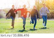 Cheerful teens running on green lawn. Стоковое фото, фотограф Яков Филимонов / Фотобанк Лори