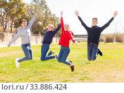 Cheerful teenages jumping in spring city park. Стоковое фото, фотограф Яков Филимонов / Фотобанк Лори