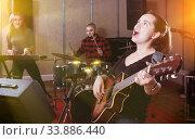 Купить «excited girl rock singer with guitar during rehearsal», фото № 33886440, снято 26 октября 2018 г. (c) Яков Филимонов / Фотобанк Лори