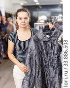 Woman choosing new overcoat in store. Стоковое фото, фотограф Яков Филимонов / Фотобанк Лори
