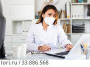 Купить «Female doctor in face mask working on laptop», фото № 33886568, снято 13 июля 2020 г. (c) Яков Филимонов / Фотобанк Лори