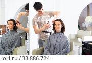 Купить «Stylist doing haircut for woman in salon», фото № 33886724, снято 2 июня 2020 г. (c) Яков Филимонов / Фотобанк Лори