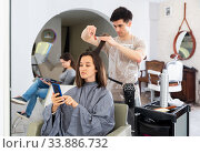 Woman getting haircut and using phone. Стоковое фото, фотограф Яков Филимонов / Фотобанк Лори
