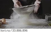 Купить «Sifting flour woman chef sieves on a black background for homemade bake. Slow motion, Full HD video, 240fps, 1080p. Process preparing of homemade bake.», видеоролик № 33886896, снято 31 мая 2020 г. (c) Ярослав Данильченко / Фотобанк Лори