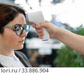 Temperature measurement by electronic infrared thermometer for office staff. Sick woman in a suit. Checking the operation of the gun-thermometer is non-contact. Prevention of the spread of covid-19. Стоковое фото, фотограф Михаил Решетников / Фотобанк Лори