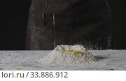 Купить «Falling egg into pile of flour on a black background. Process of preparing dough for homemade pasta. Slow motion, Full HD video, 240fps, 1080p.», видеоролик № 33886912, снято 9 июля 2020 г. (c) Ярослав Данильченко / Фотобанк Лори