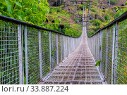 Купить «Close-up of a swinging suspension bridge leading to the cave city of Khndzoresk over a gorge in the mountains of Armenia», фото № 33887224, снято 8 июня 2018 г. (c) Константин Лабунский / Фотобанк Лори