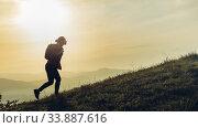 Купить «Трекинг в горах. Девушка взбирается на гору на фоне живописного пейзажа и рассвета», фото № 33887616, снято 2 мая 2019 г. (c) Сергей Тиняков / Фотобанк Лори