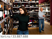 Купить «Ordinary woman customer buying bottle of wine», фото № 33887688, снято 15 июля 2020 г. (c) Яков Филимонов / Фотобанк Лори
