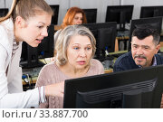 Купить «Business woman explaining something to coworkers, pointing at computer», фото № 33887700, снято 20 февраля 2019 г. (c) Яков Филимонов / Фотобанк Лори