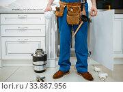 Male plumber installing water filter in kitchen. Стоковое фото, фотограф Tryapitsyn Sergiy / Фотобанк Лори