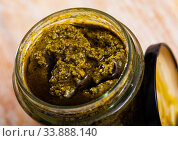 Organic pesto sauce in glass jar on wooden surface. Стоковое фото, фотограф Яков Филимонов / Фотобанк Лори