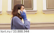 Купить «woman in face mask calling on smartphone in city», видеоролик № 33888944, снято 25 мая 2020 г. (c) Syda Productions / Фотобанк Лори