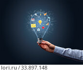 Hand holding light bulb on dark background. New apps concept. Стоковое фото, фотограф Zoonar.com/rancz / easy Fotostock / Фотобанк Лори