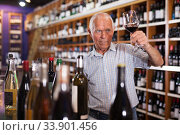 Man inspecting wine in wine store. Стоковое фото, фотограф Яков Филимонов / Фотобанк Лори