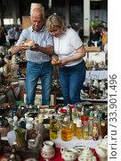 Купить «Glad man and woman choosing interesting souvenirs at traditional flea market», фото № 33901496, снято 11 мая 2019 г. (c) Яков Филимонов / Фотобанк Лори
