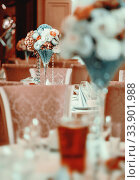 Beautifully decorated of luxury wedding banquet at restaurant. Bouquet of flowers on served tables. Life event, wedding or birthday reception, no people. Стоковое фото, фотограф Alexander Tihonovs / Фотобанк Лори
