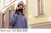 Купить «woman in headphones, mask and gloves in city», видеоролик № 33902500, снято 28 мая 2020 г. (c) Syda Productions / Фотобанк Лори
