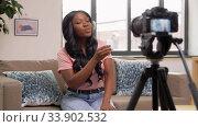 Купить «female video blogger showing earphones to camera», видеоролик № 33902532, снято 24 мая 2020 г. (c) Syda Productions / Фотобанк Лори