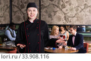 Successful young female chef standing in restaurant hall, welcoming guests. Стоковое фото, фотограф Яков Филимонов / Фотобанк Лори