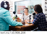 Купить «Multinational group of cheerful young adults emotionally discussing in radio studio», фото № 33908204, снято 16 марта 2019 г. (c) Яков Филимонов / Фотобанк Лори