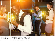 Купить «Glad Afro man and colleagues in laser tag room», фото № 33908248, снято 4 апреля 2019 г. (c) Яков Филимонов / Фотобанк Лори