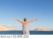 Купить «Happy carefree woman rising arms, wearing beautiful striped summer dress enjoying late afternoon on white pabbled beach on Pag island, Croatia», фото № 33909320, снято 14 июля 2019 г. (c) Matej Kastelic / Фотобанк Лори