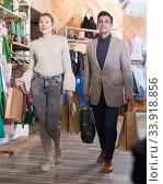 Купить «Smiling couple is satisfied of purchases and walking with package», фото № 33918856, снято 12 марта 2018 г. (c) Яков Филимонов / Фотобанк Лори