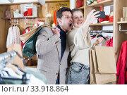 Купить «Smiling couple is satisfied of purchases and taking selfie», фото № 33918864, снято 12 марта 2018 г. (c) Яков Филимонов / Фотобанк Лори