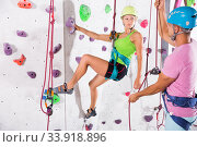 Купить «Couple of alpinist practicing in pair indoor rock-climbing», фото № 33918896, снято 14 июля 2020 г. (c) Яков Филимонов / Фотобанк Лори